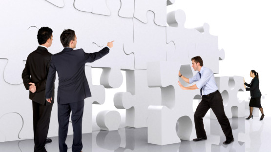 business teamwork – business men making a puzzle